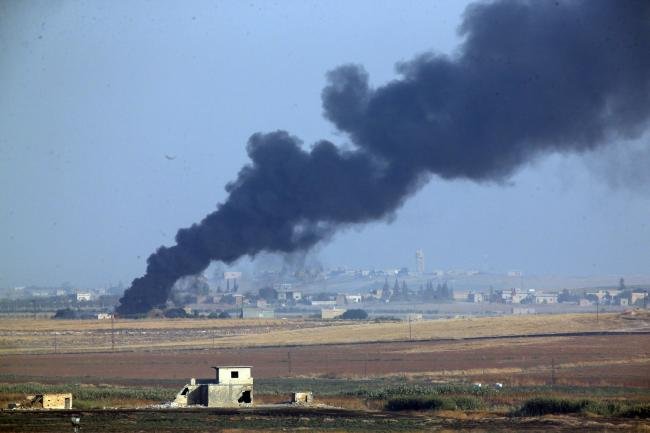 Smoke billows from a fire inside Syria during bombardment by Turkish forces