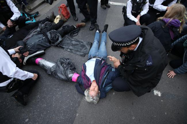 Protesters from Extinction Rebellion (XR) block a road in Westminster, London. PA Photo. Picture date: Monday October 7, 2019. See PA story ENVIRONMENT Protests. Photo credit should read: Yui Mok/PA Wire.