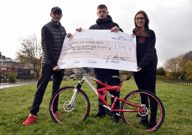 Anthony Farrer and Haydn Moor present a cheque to Vicky Bowden, from the Yorkshire Air Ambulance, following their charity bike ride