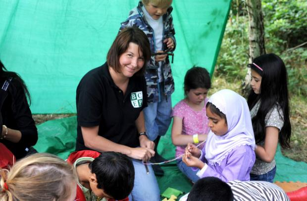 Environmental play worker Jennifer Scott helps children with natural crafts