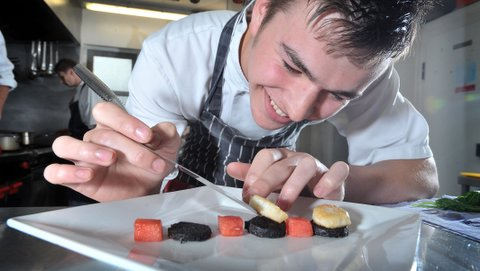 Commis chef Zak Dearden delicately assembles a dish of pan-fried king           scallops with black pudding, roasted watermelon and balsamic syrup