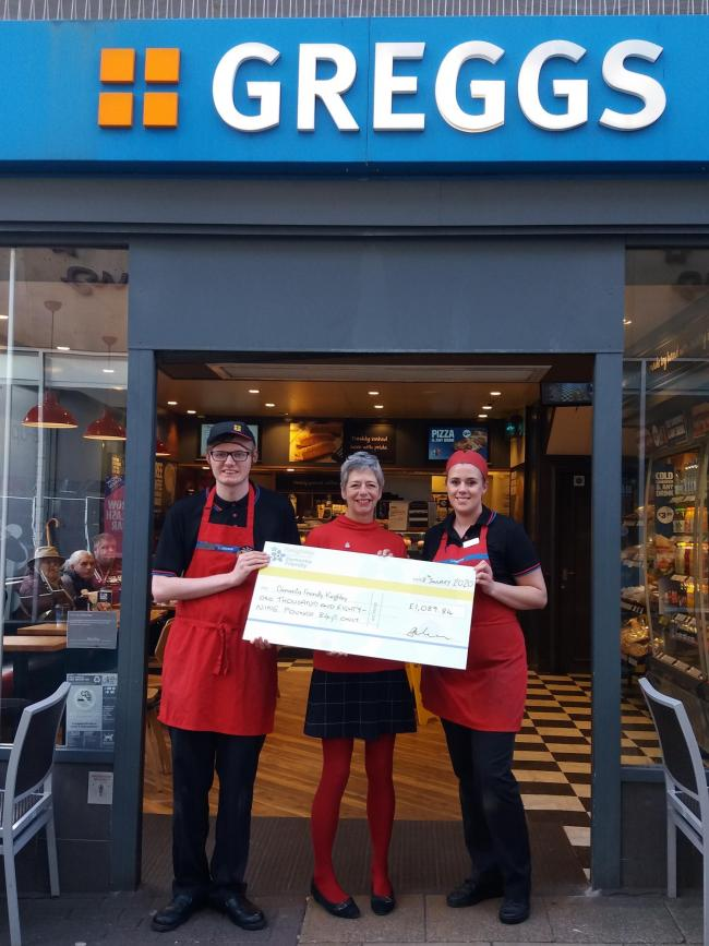 Dementia Friendly Keighley trustee Maggie Marsden receiving a cheque from Keighley Greggs