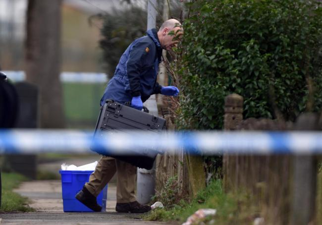 A bomb squad technician investigating a house on Sutton Avenue yesterday.