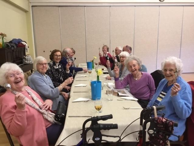 Members of Clarke Foley's Thursday Lunch Club wave their new spoons in delight