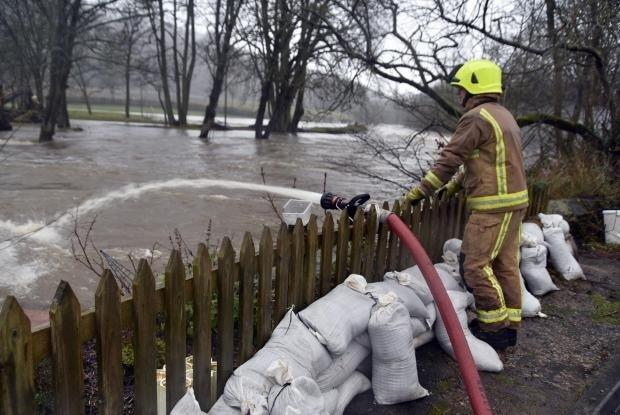 A firefighter pumping water at Crossflatts during Storm Ciara, as emergency services prepare for more heavy rain