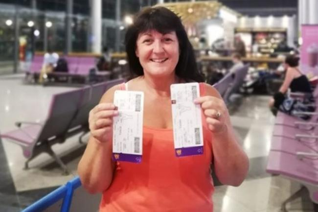 Cheryl Baxter holding her boarding passes for her flight home to the UK
