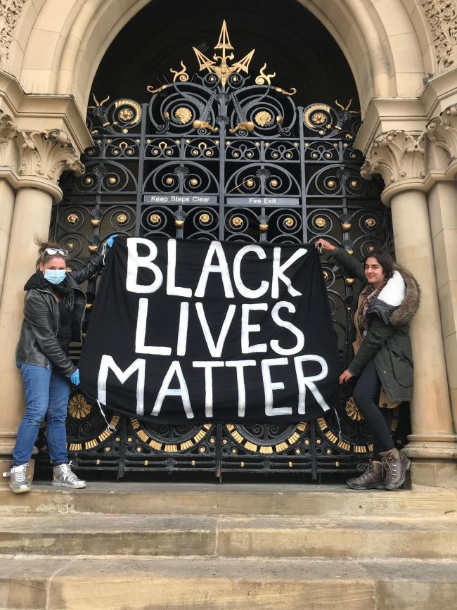 Mother and daughter Vic Brett (left) and Flo Brett-Iqbal (right), from Saltaire, hold a Black Lives Matter flag outside City Hall