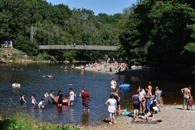 People enjoying the River Wharfe in Ilkley in summer 2020