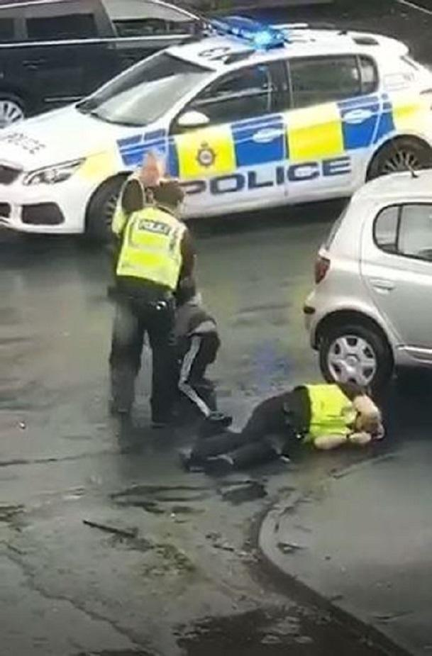 A man is detained as a police officer lies on the ground after being run down