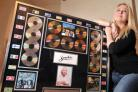 Holly Faye with her dad's gold discs and flags denoting countries where Smokie have had hits