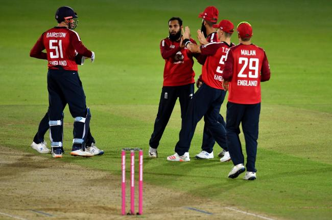 Jonny Bairstow and Dawid Malan are among those lining up to congratulate Adil Rashid after he took the wicket of Australia's Steve Smith in a T20 International match last September. Picture: Glyn Kirk/NMC Pool/PA Wire.