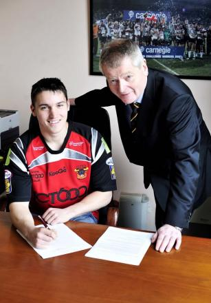 Cain Southernwood signs his Bulls contract, watched by chairman Peter Hood