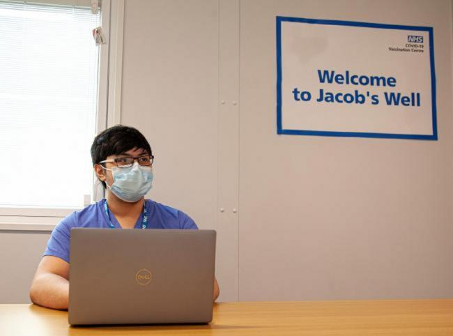 Healthcare assistant Vince Season welcomes people to Jacob's Well NHS Covid-19 vaccination centre