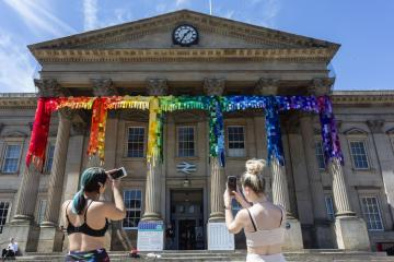 Stunning pictures show West Yorkshire train station transformed with 15,000 rainbow knitted squares