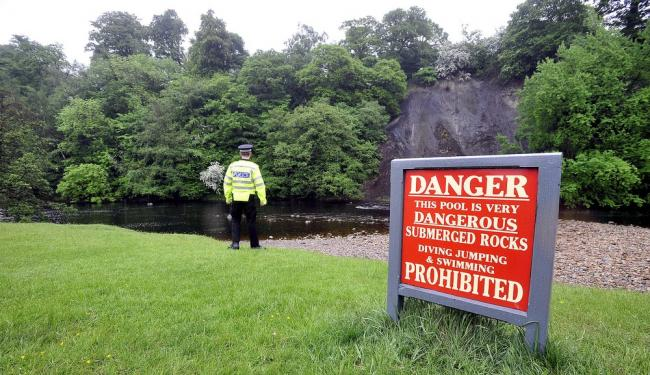 A police officer stands guard at the scene of the tragedy on the River Wharfe at Bolton Abbey