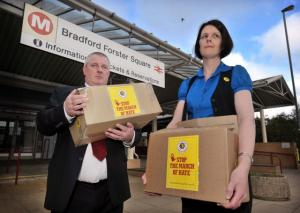 Paul Meszaros and Lorraine Fitzsimons hold boxes containing the anti-EDL petition at Forster Square Station