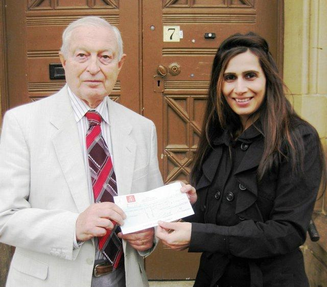 Synagogue chairman Rudi Leavor receiving a cheque from Action for Business's Shakeela Khaliq