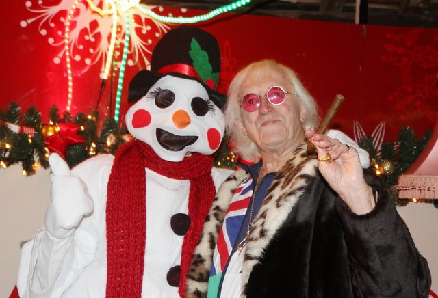 Sir Jimmy Savile with a snowman at the Bingley Christmas lights switch-on