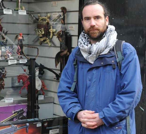 The Rev Chris Howson outside Barkers window display which includes a crossbow