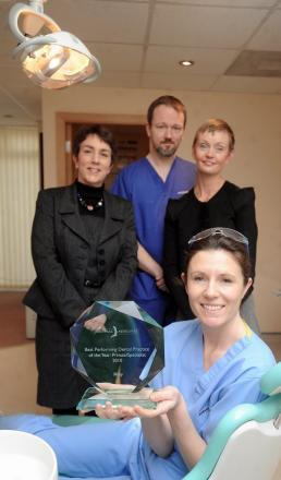 Pictured are (front) dental nurse Kirsty Whitaker and (back from left) receptionist Carolyn Hayes, dentist Martin Harris, and practice manager Jill Dean