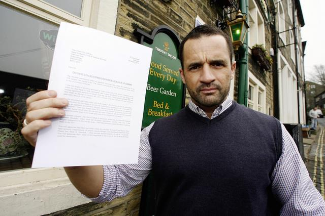 Nick Hindle outside his pub with his letter to the fire service
