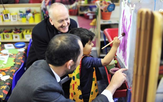 The Bishop of Bradford, the Right Reverend Nick Baines, with two-year-old Haseeb Ahmed and Rashid Iqbal, deputy director of the Children's Society
