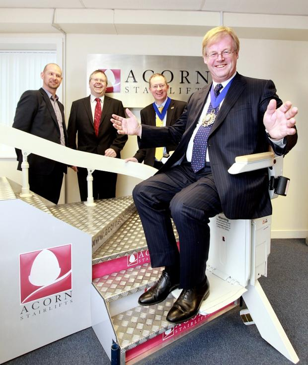 Lord Mayor of London David Wootton tries out one of Acorn Stairlifts' products, with Nick Wilson and Dave Belmont, from Acorn, and Bradford Chamber of Commerce president Stephen Wright looking on