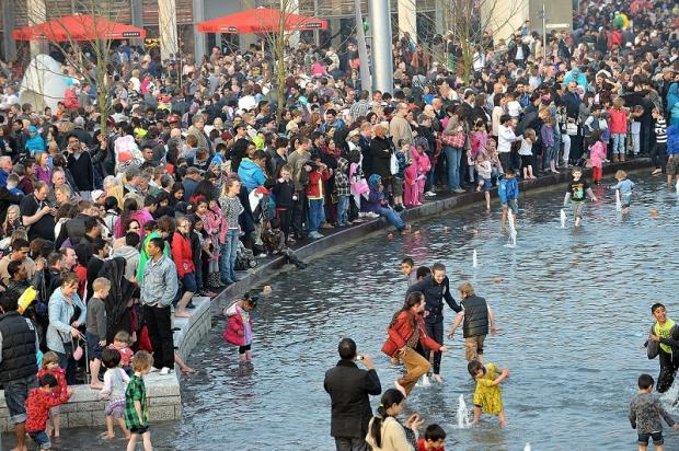 Crowds splash in the mirror pool at the City Park opening today
