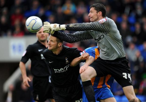 City keeper Matt Duke punches clear against Shrewsbury with Lee Bullock lending assistance