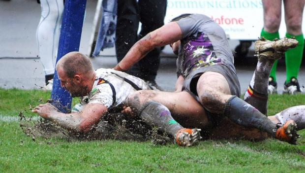 MUD SLIDE: Michael Platt crosses in the corner for the Bulls' only try of the match