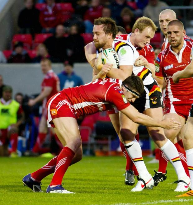 Bryn Hargreaves tries to escape the clutches of his Salford opponents