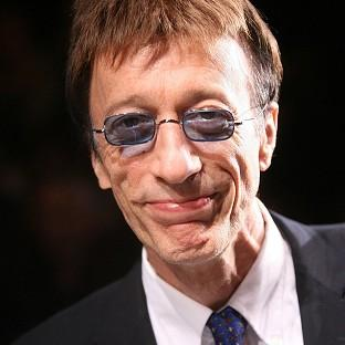 Fans have flocked to pay tribute to Bee Gees star Robin Gibb at his funeral in Oxfordshire