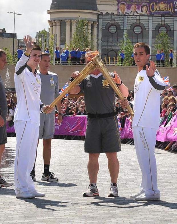 Thomas Stokes (left) passes the Olympic Flame to Jamie Brown in City Park