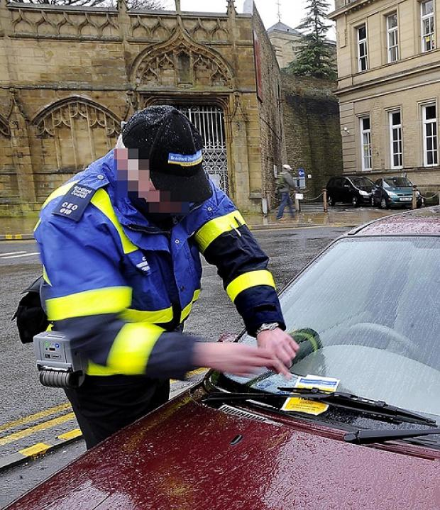 A Bradford Council parking warden  tickets a car caught on double yellow lines