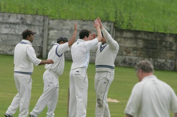 Crossflatts fielders celebrate with bowler Jim O'Hara, third left, after a wicket at Thornton-in-Craven