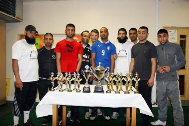 Champions Premier Youth show off their trophies with NADA duo Nazim Ali, centre, and Tahir Aslam, left, as well as 5Alive Soccer Centre manager Paul Evans, back