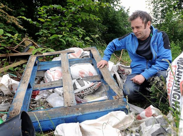Concerned resident Andy Egan with some of the rubbish dumped at the site