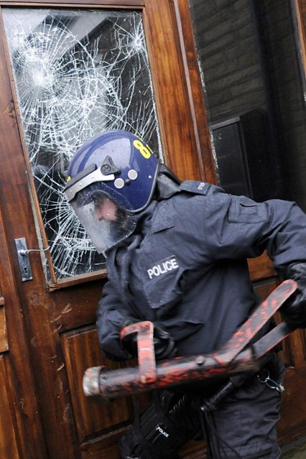 Police try to gain entry to a property during Operation Sabredale