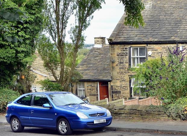 A car outside the home in Woodhall Lane Calverley where two bodies were found