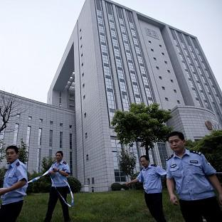 Police officers place a cordon around the Hefei City Intermediate People's Court for the murder trial of Gu Kailai (AP/Andy Wong)