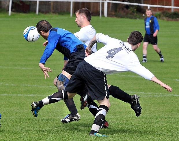 A Queensbury player is the meat in a sndwich at Thornton United