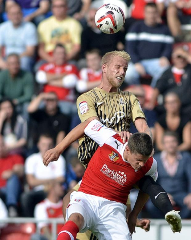 NOT SO SOLID CREW: Centre back Andrew Davies outjumps Rotherham's Alex Revell on a day when the normally resilient Bantams back four were found wanting