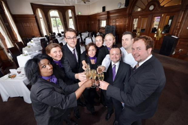 Staff at the Great Victoria Hotel raise a glass, led by general manager Simon Grybus (right)