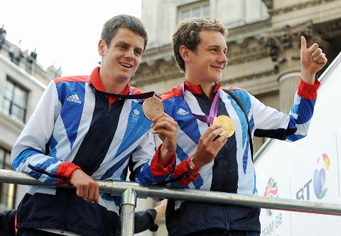 Jonathan (left) and Alistair Brownlee wave to the crowds wearing their medals during a parade celebrating Britain's Olympic and Paralympic sporting heroes, near Mansion House, London.
