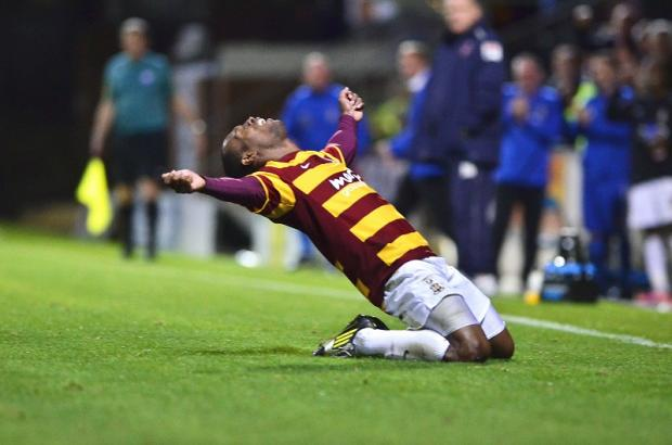 Kyel Reid knee-slides his way over to the City fans to celebrate his first goal at Valley Parade
