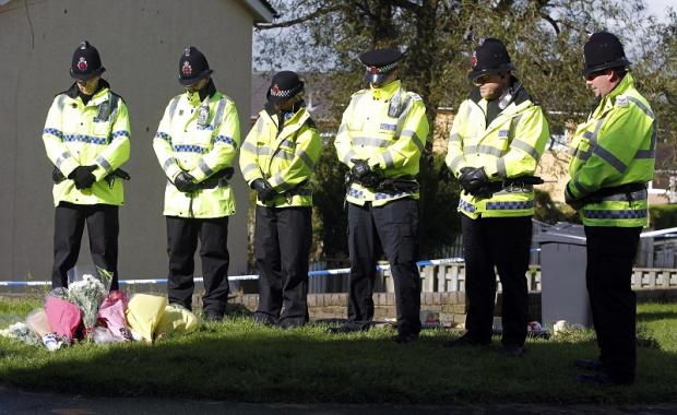 Officers observe a moment of silence near the house in Hattersley, Manchester, where PCs Fiona Bone and Nicola Hughes died
