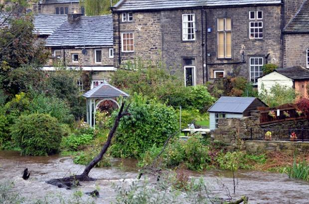 Homes by the side of the rising River Aire at Bingley yesterday