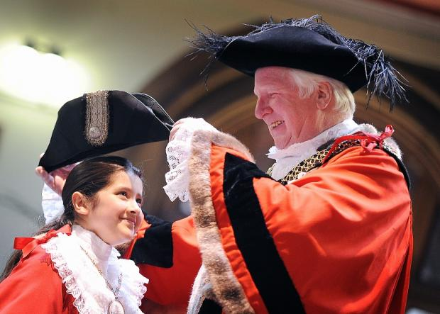 Bradford Telegraph and Argus: Lord Mayor Councillor, Dale Smith helps the mini Lord Mayor for the day, Ruqayyah Rauf, from Girlington Primary School, with her robes at the start of Old People's Week in City Hall