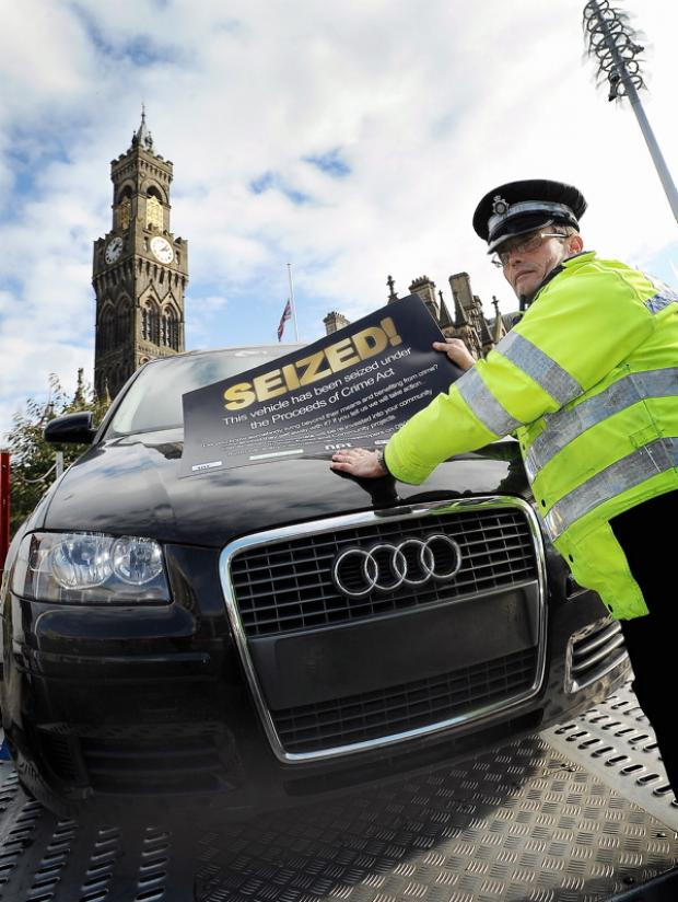 A PCSO puts a 'Seized' poster onto the Audi in Centenary Square