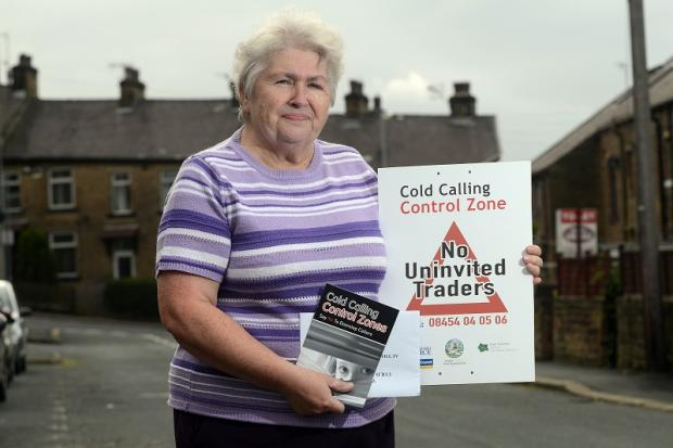 Sue Kenworthy with one of the signs which ban door to door traders from streets in Windhill, Shipley